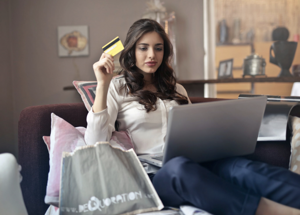 photo of woman sitting on couch with credit card